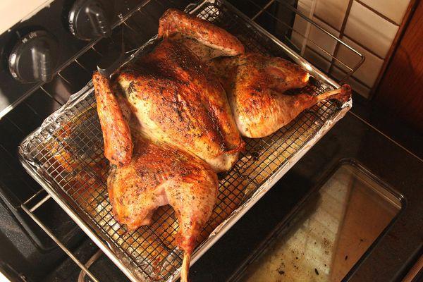 Herb-Rubbed Crisp-Skinned Butterflied Roast Turkey on a rack in the oven.