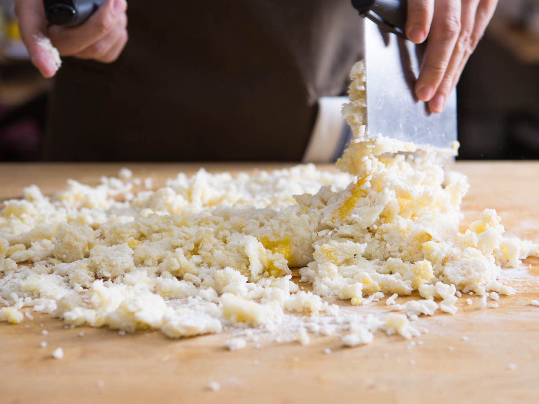 Using a bench scraper to cut flour into potato for gnocchi