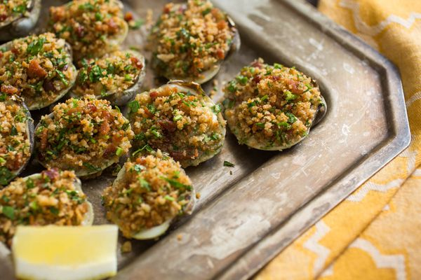 A tray of easy, ultimate Clams Casino with a lemon wedge.