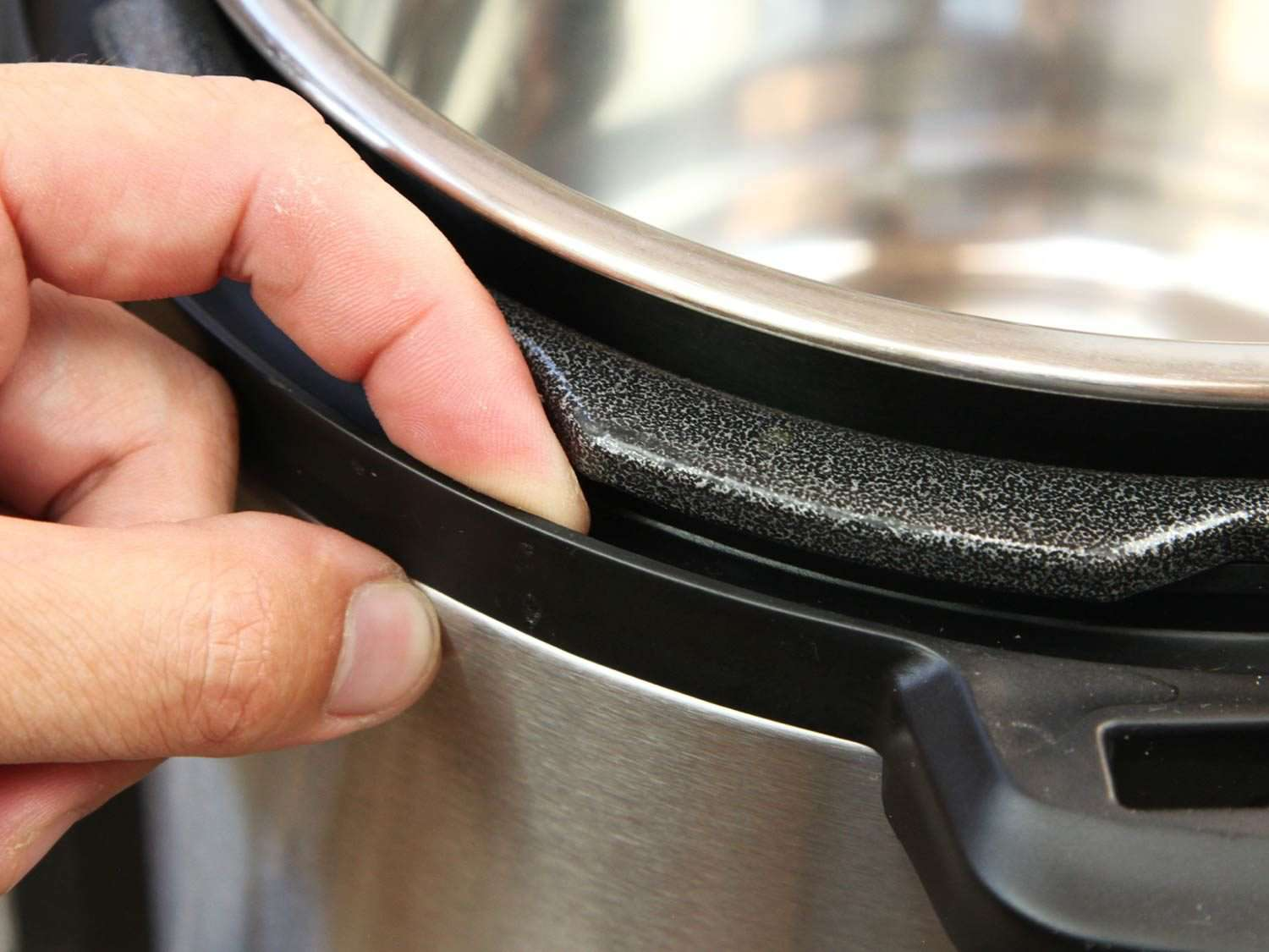 Finger in narrow crevice along lip of Instant Pot