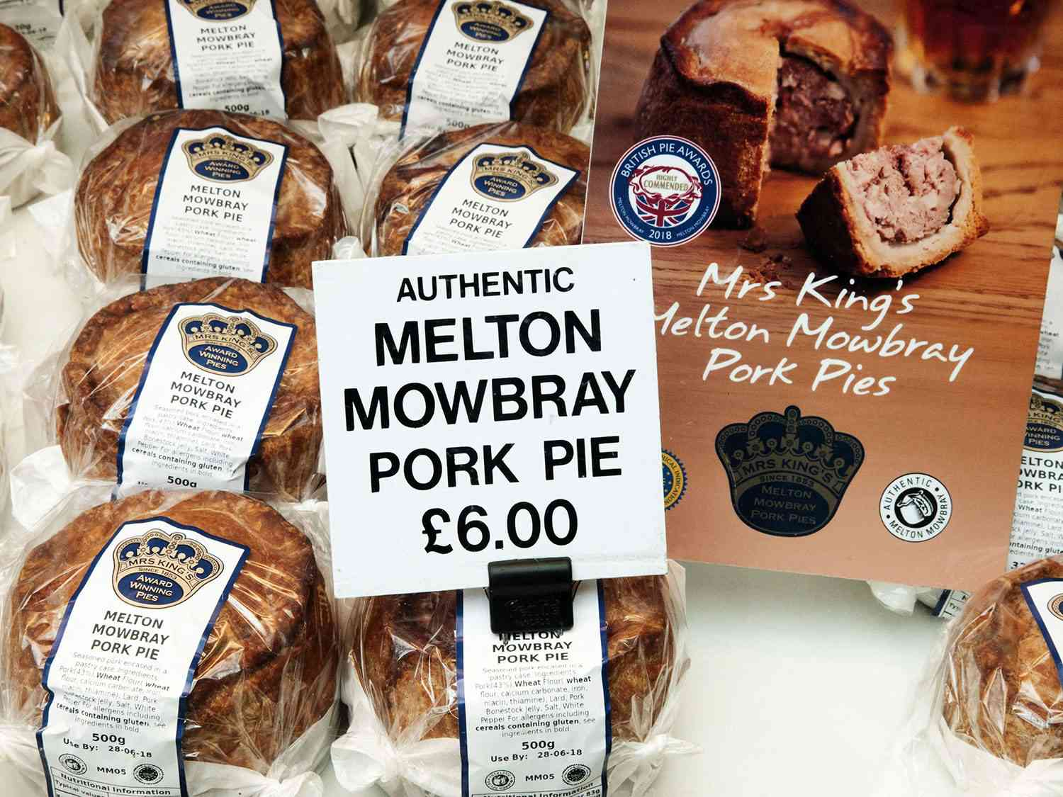 A display of wrapped pork pies for sale, with a sign that says