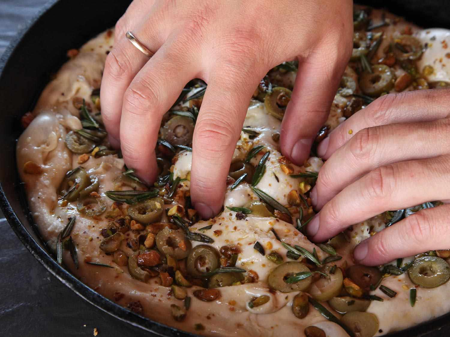 Pressing olives and pistachios into focaccia dough with fingertips