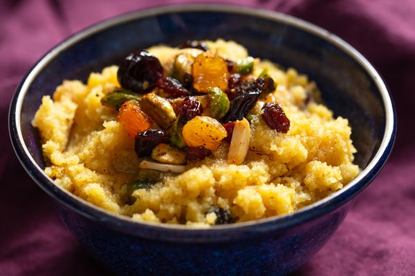 Bowl of semolina halva topped with spiced nuts and dried fruit