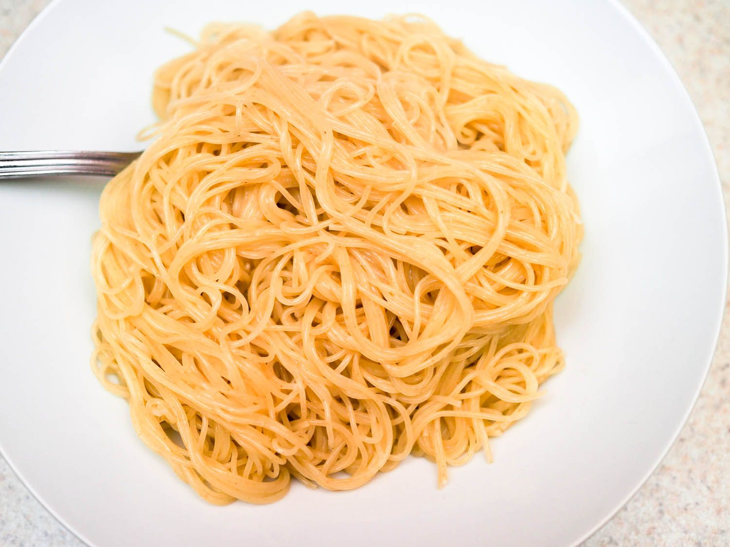 A plate with a pile of angel hair pasta cooked with baking soda.