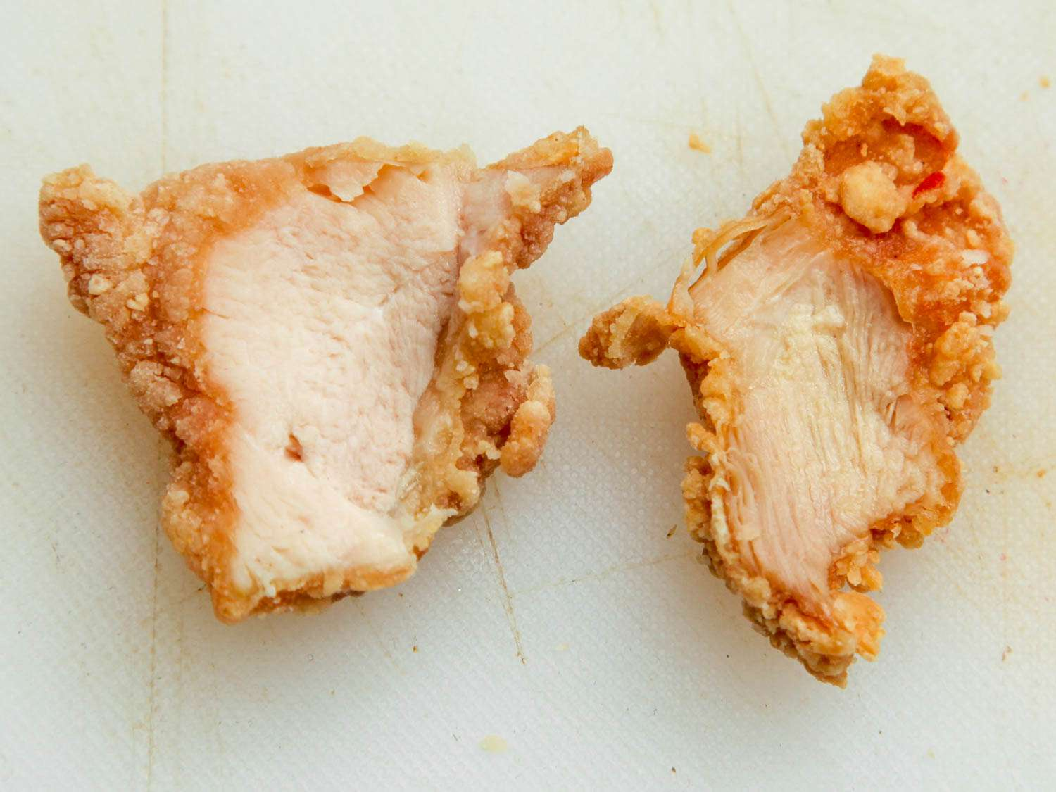 Fried chicken breast (left) and fried chicken thigh (right) side-by-side on white cutting board.