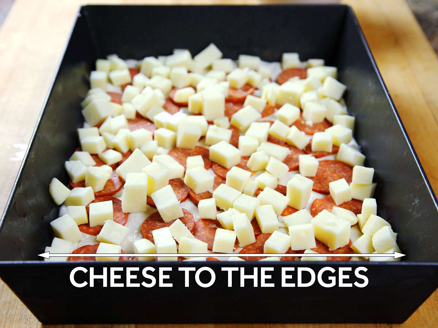 Cubed cheese spread to the edge of a Detroit-style pizza