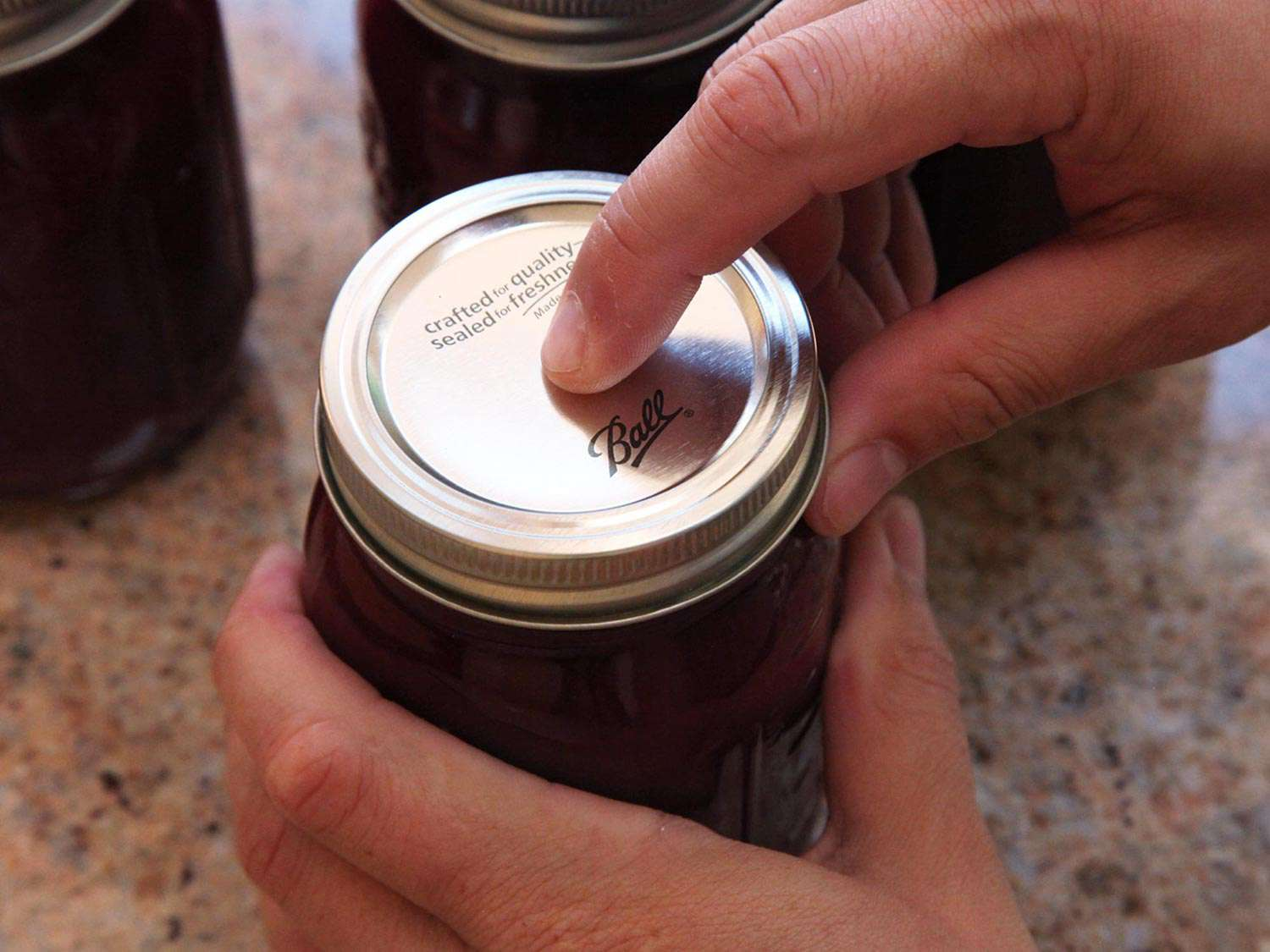 A fingertip pressing on the center of the metal lid on a sealed jar of plum jam