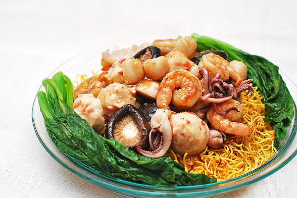 A glass plate with Asian greens and crispy pan-fried noodle cakes with seafood.