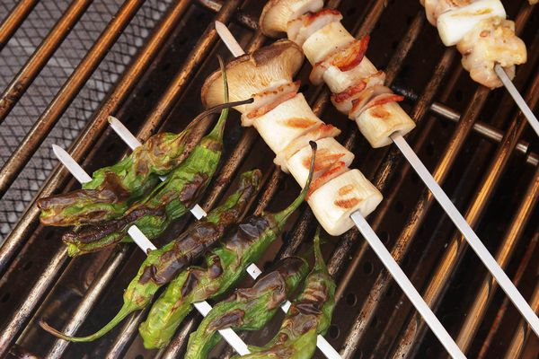 peppers, mushrooms, scallions, and chicken on skewers on a grill