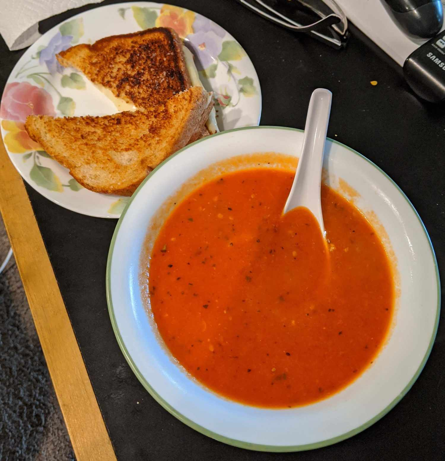 Bowl of tomato soup with a grilled cheese on a plate alongside