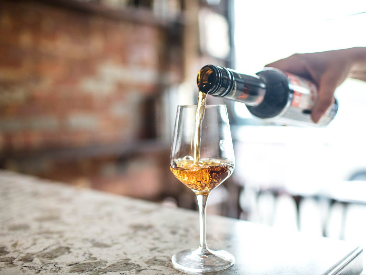 An amber-colored Oloroso sherry being poured into a wineglass