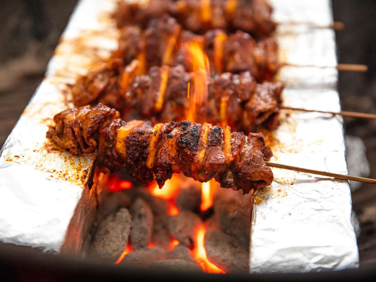 Flames licking up the sides of al pastor skewers