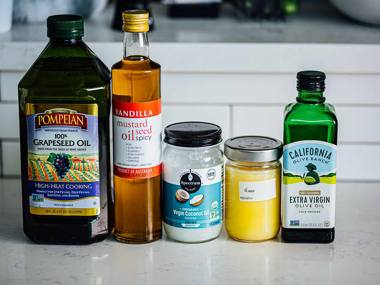 Grapeseed oil, mustard seed oil, coconut oil, ghee, and extra virgin olive oil in a row on a kitchen counter