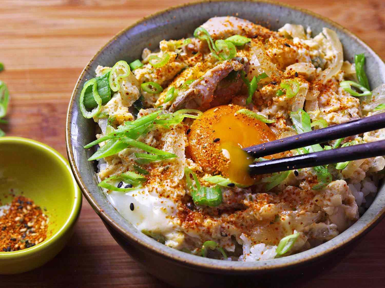 Breaking open an egg yolk in a bowl of oyakodon.