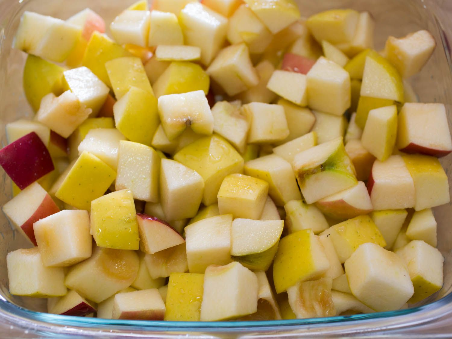 Chopped red and yellow apples in a glass baking dish