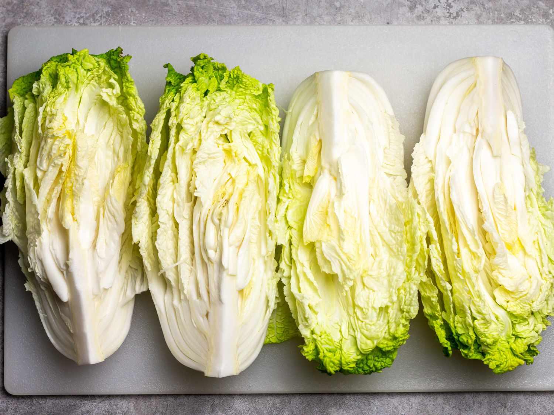 a head of napa cabbage cut into 4 quarters in preparation for baechu kimchi