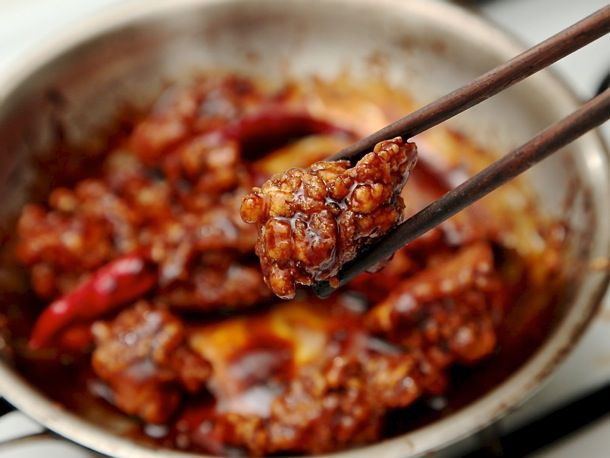 Using chopsticks to hold up a piece of General Tso's chicken above skillet of chicken.