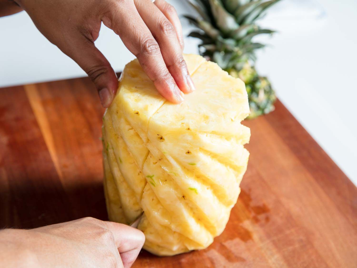 A knife slicing a pineapple in half.