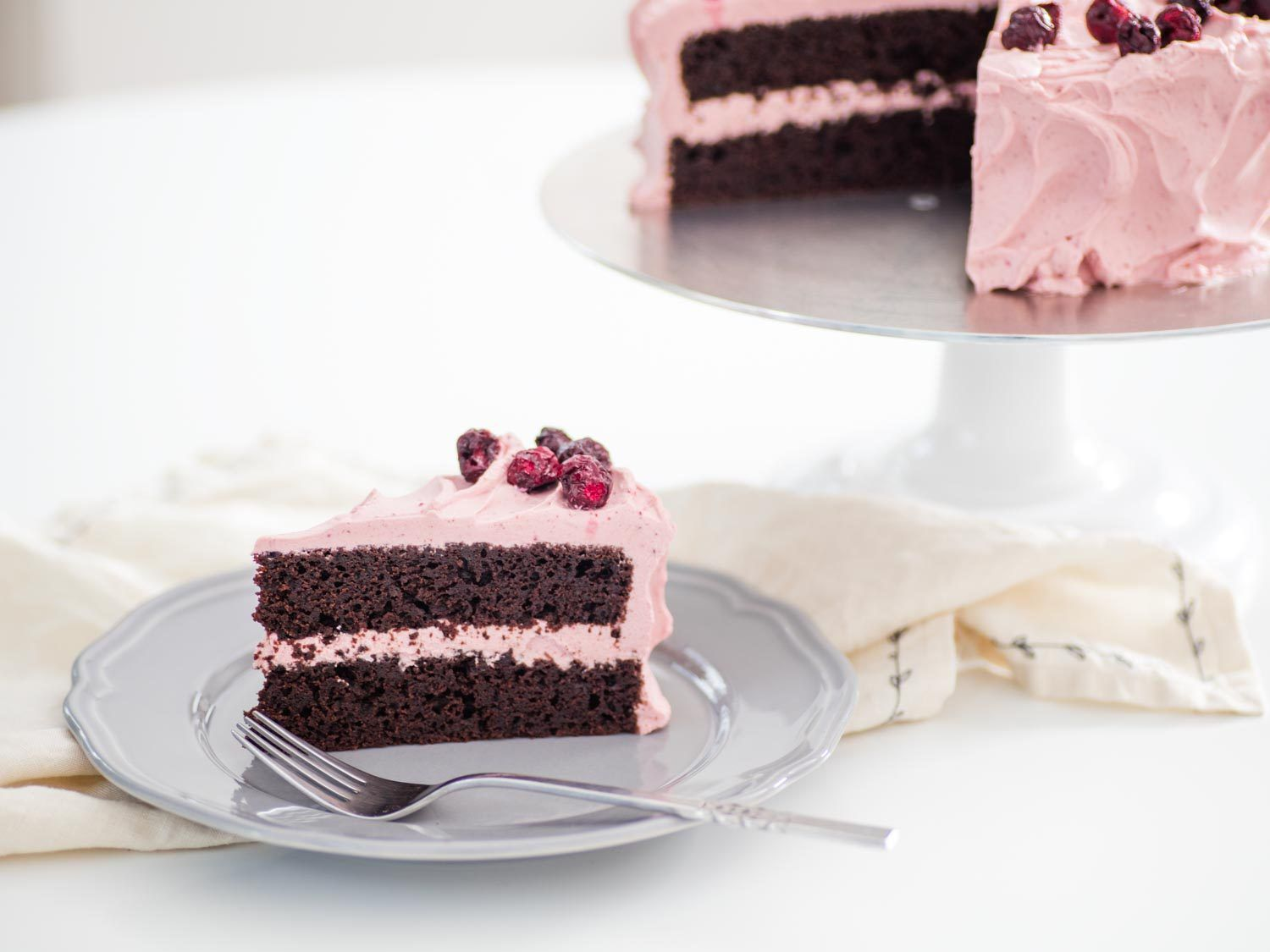 a slice of a two-layer chocolate cake with pale pink cherry whipped cream on a plate, with the remaining cake on a stand in the background