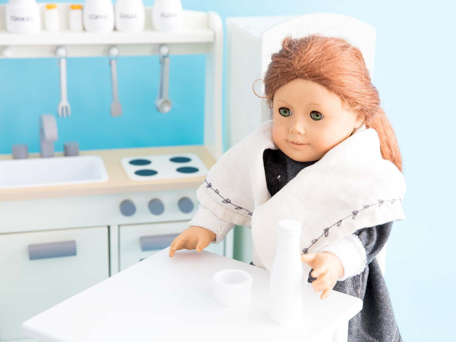 A Felicity doll standing at the corner in a white doll kitchen, over a small white bowl and bottle of milk