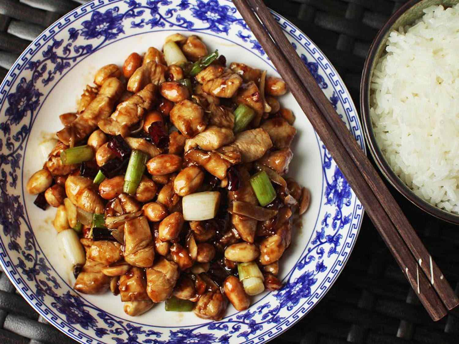 Kung pao chicken in a blue and white bowl with chopsticks. White rice in a bowl on the side.