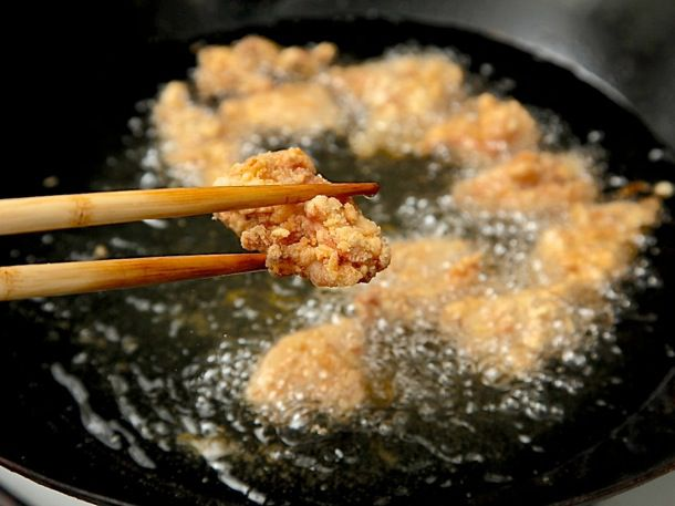 Holding a piece of fried chicken with chopsticks above wok filled with hot oil and frying chicken.