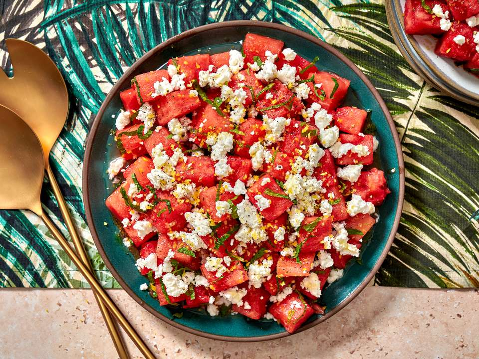 Watermelon, feta, and mint salad in a bowl on a colorful tropical print napkin