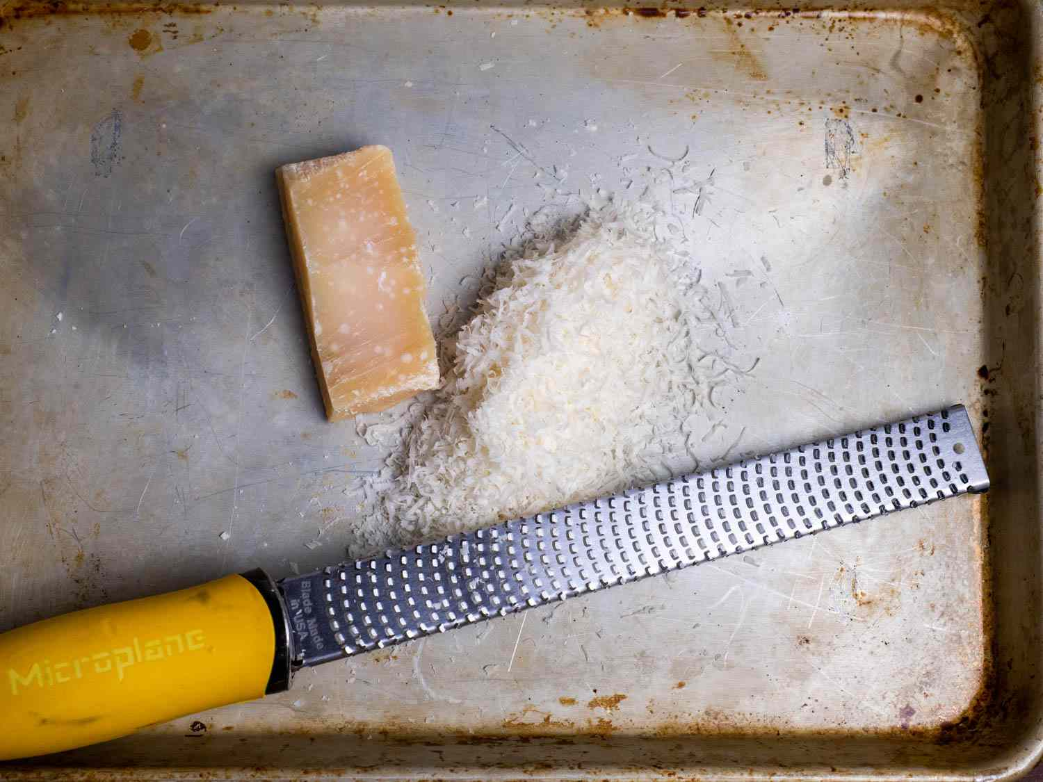 A Microplane alongside a pile of finely grated cheese and a chunk of Parmesan