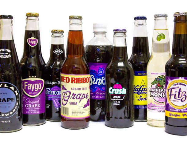 A collection of assorted grape sodas in bottles.