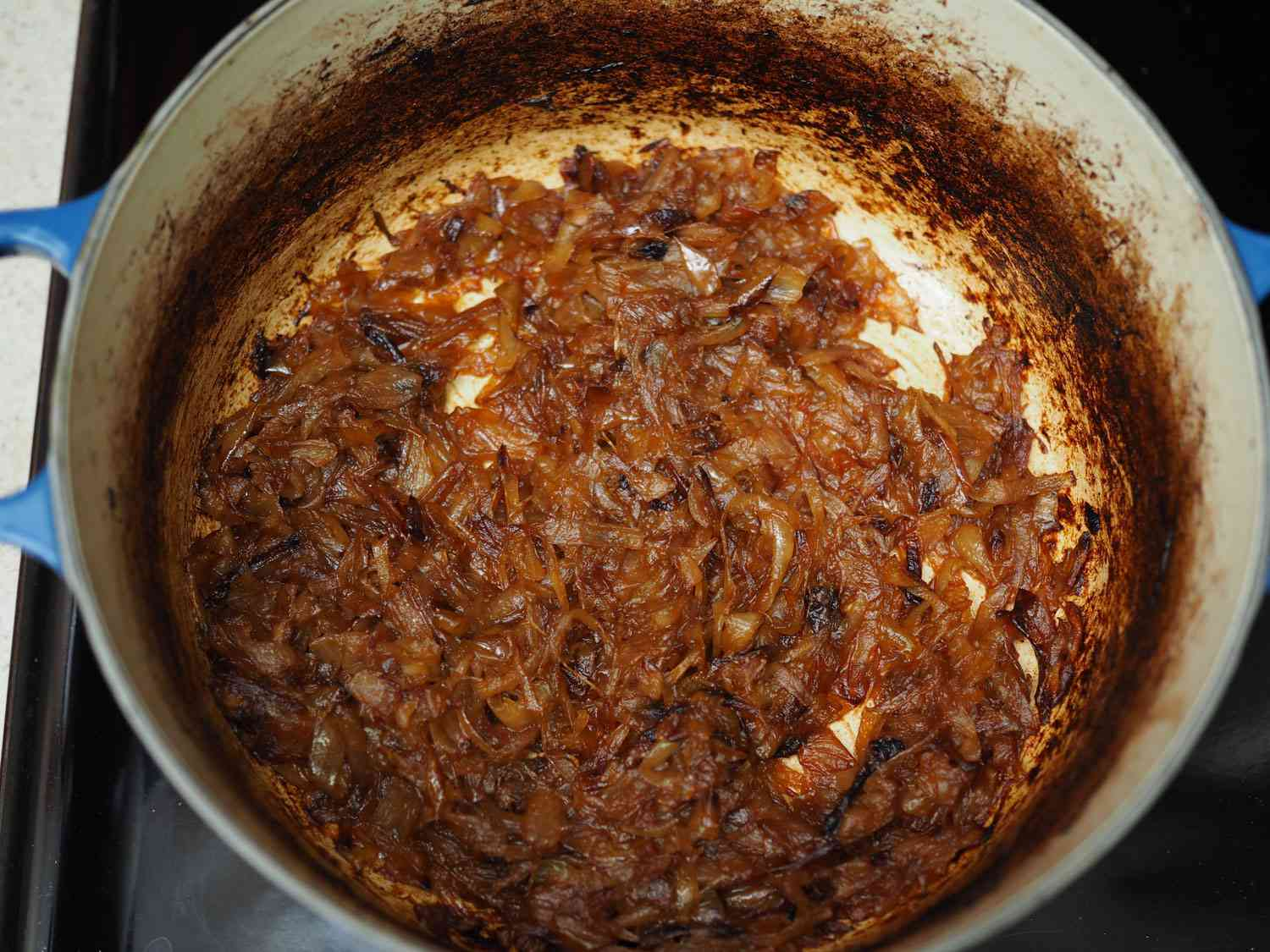 Dutch oven filled with onions that have been caramelized in the oven.