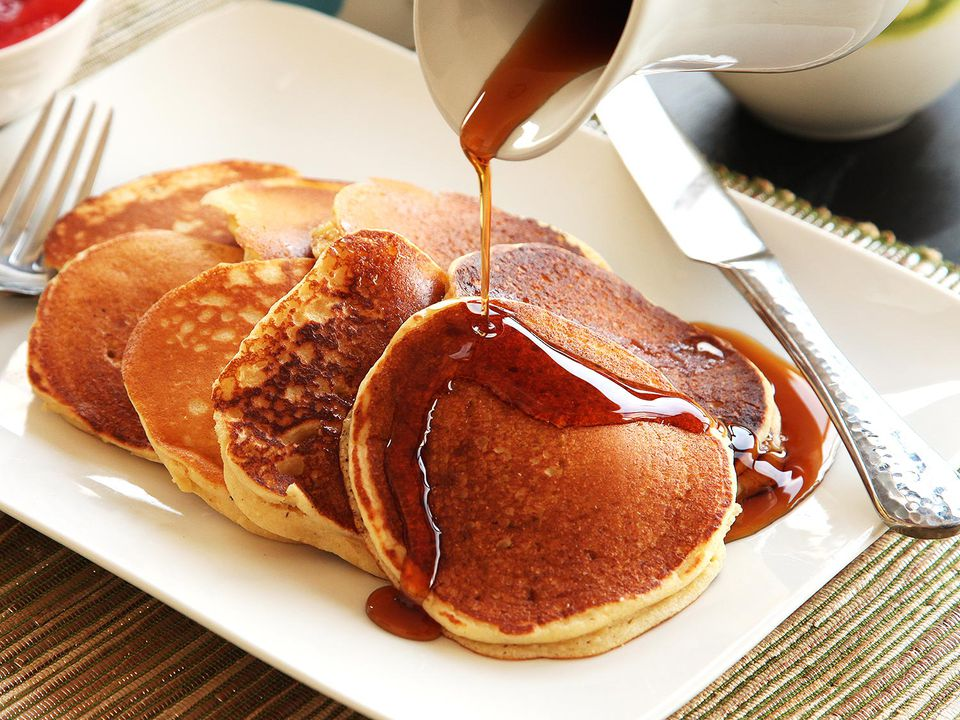 Syrup being poured over a plate of buttermilk pancakes