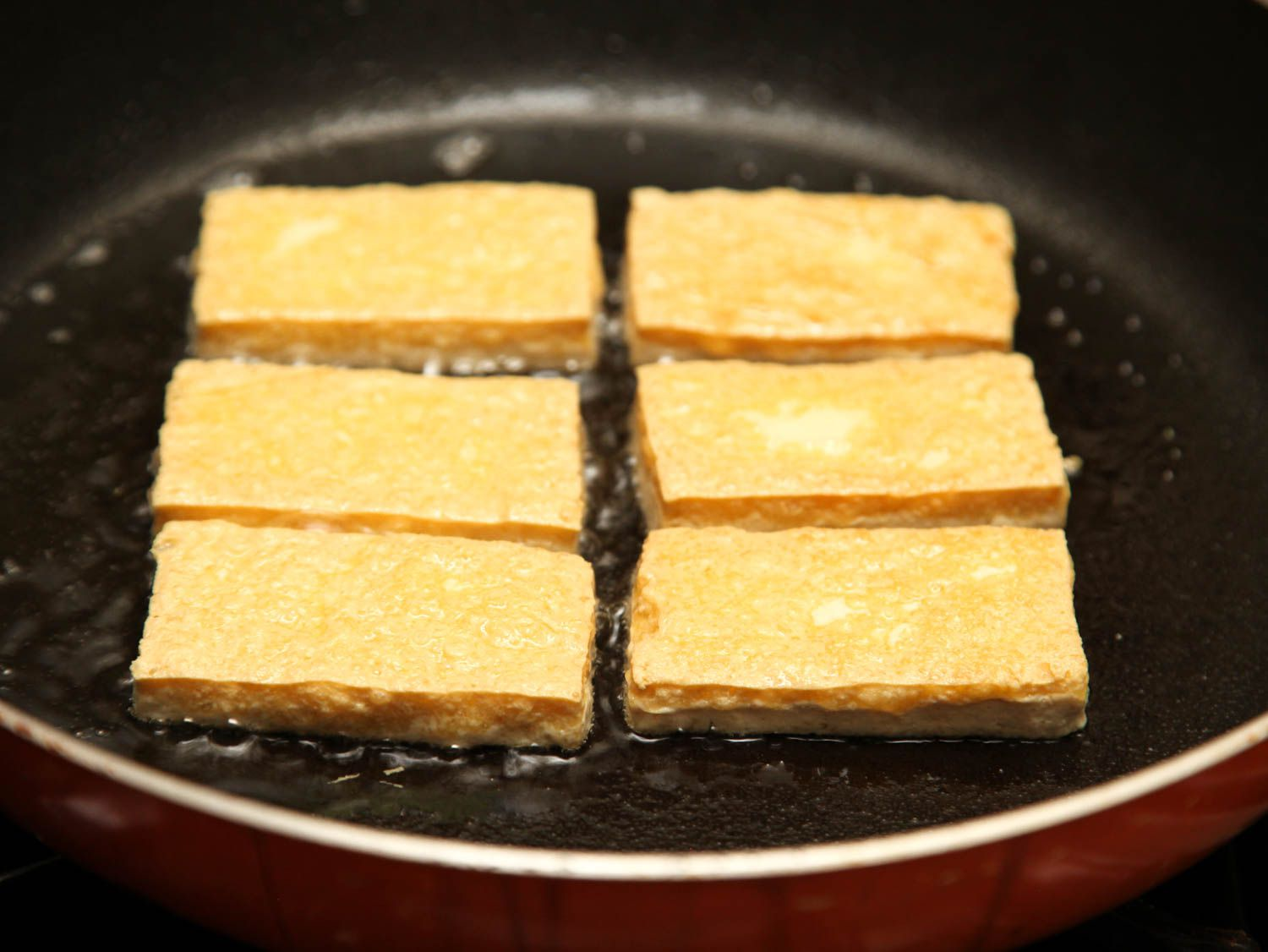 Tofu frying in a skillet, browned on top side.