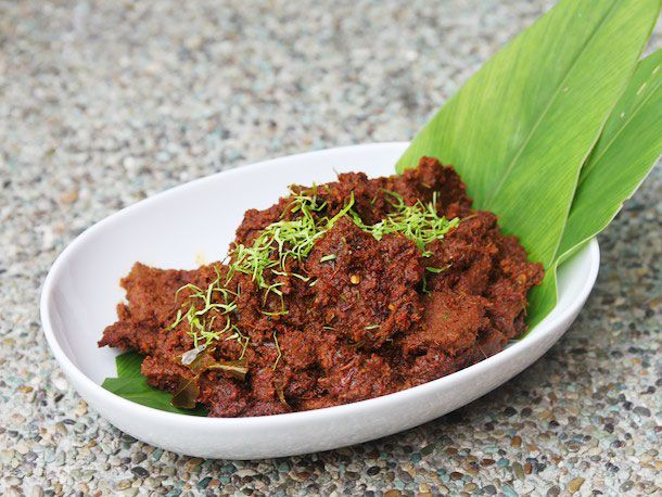 Beef rendang in an oval white bowl