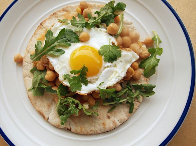 Harissa chickpeas with fried egg, served on top of pita bread and garnished with arugula and cilantro.