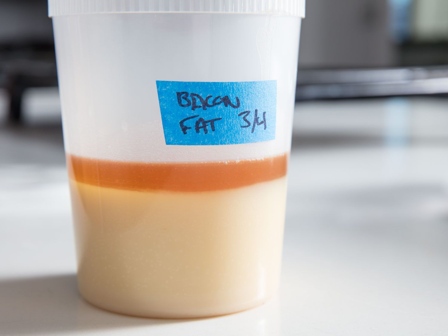 A plastic container of partly solidified bacon fat, labeled