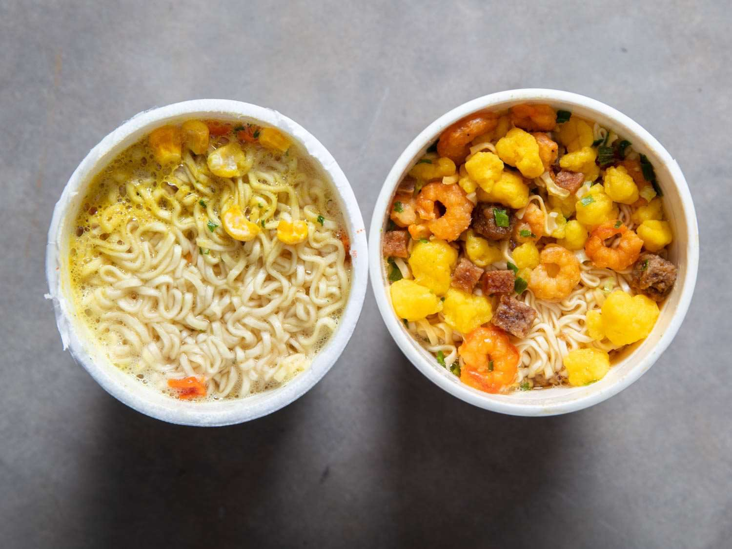 Overhead comparison shot of American Chicken Cup Noodles cup and Japanese