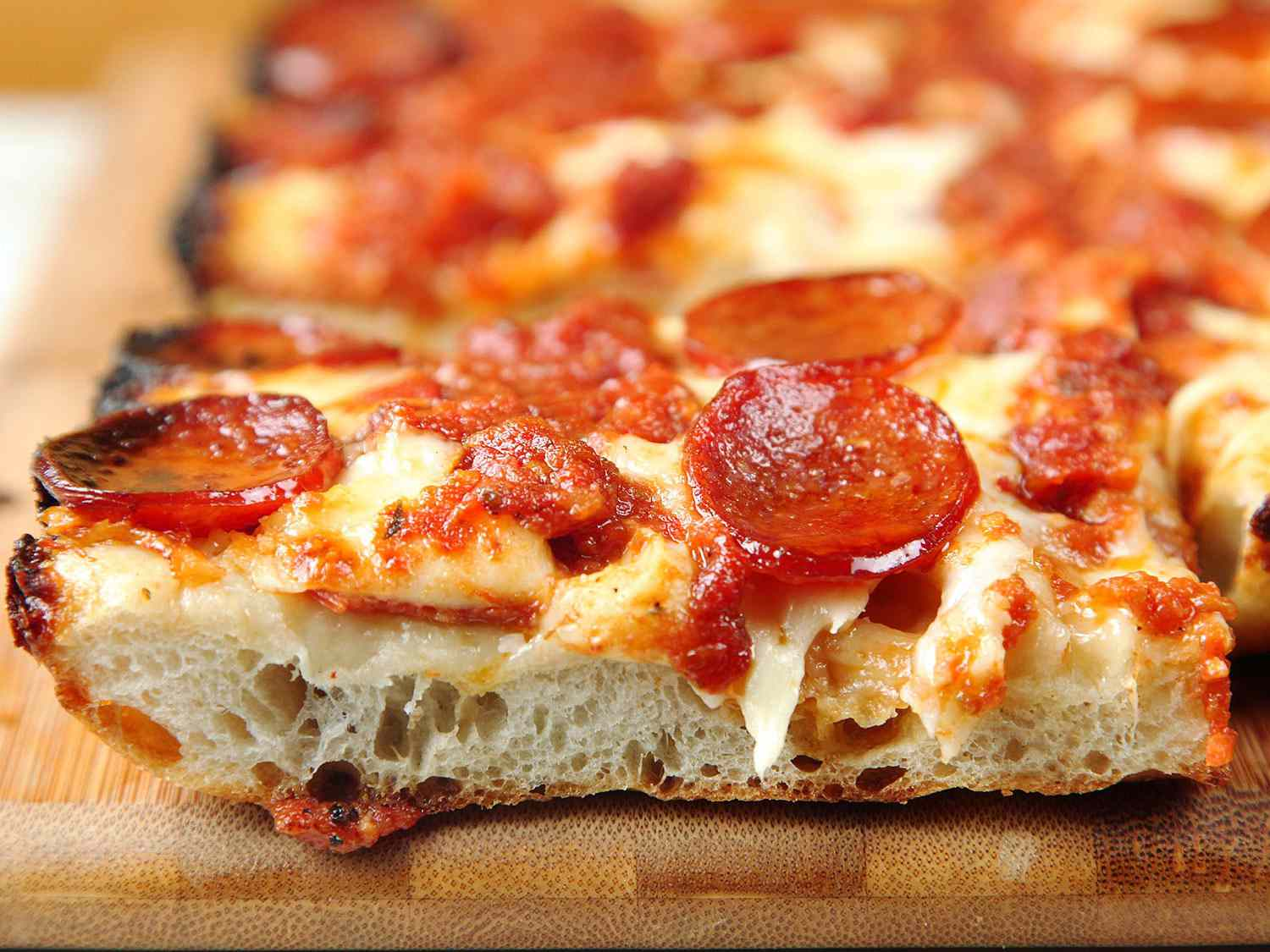 A slice of Detroit-style pizza resting on a cutting board