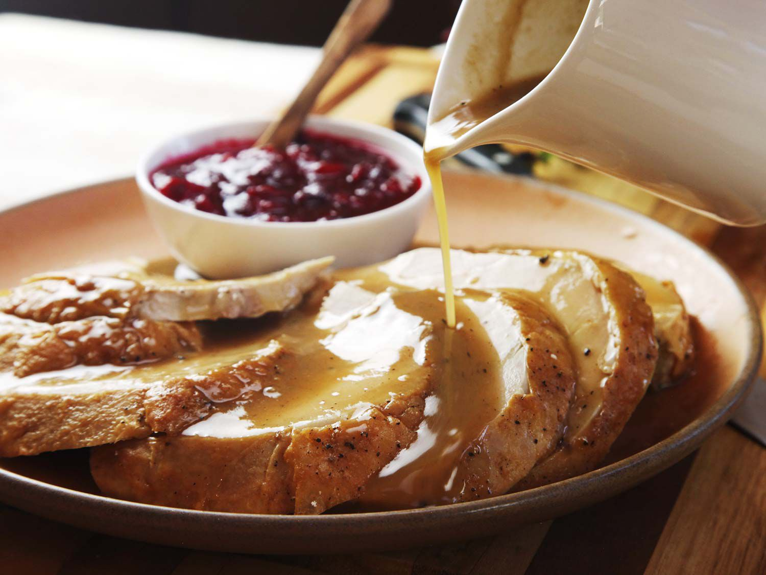 Pouring gravy from a pitcher over a platter of sliced roasted turkey breast meat, with a bowl of cranberry sauce in the background.