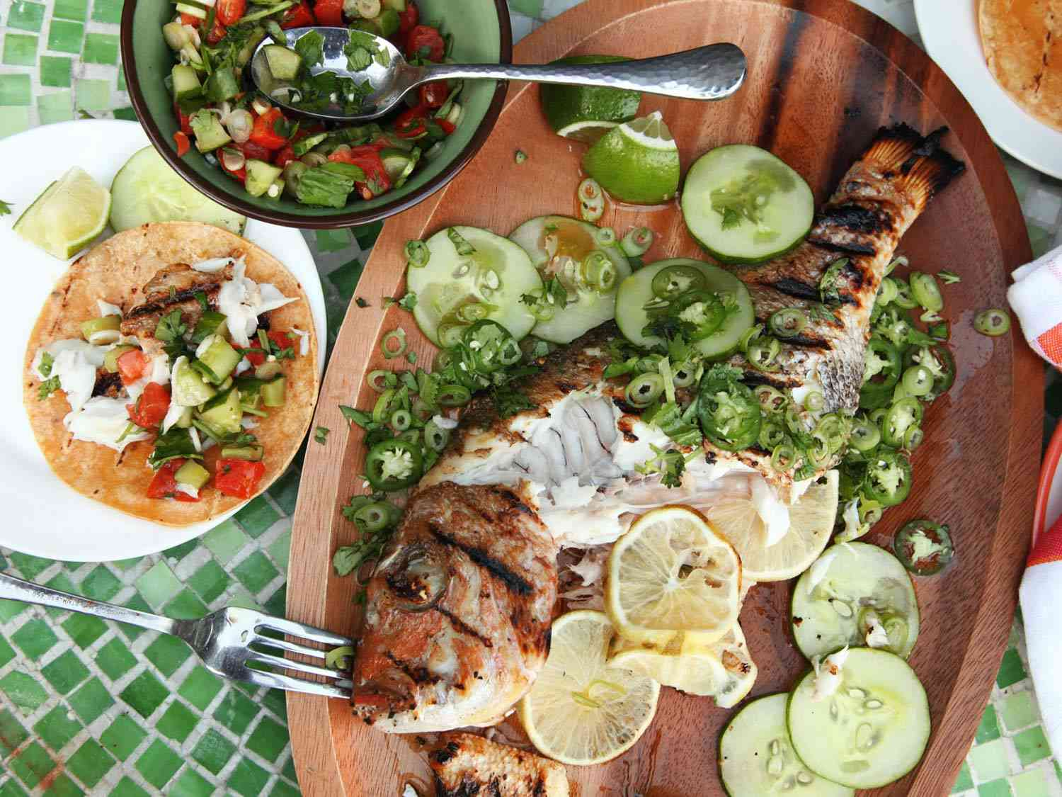 Grilled whole fish on a platter with peppers, cucumber slices, and lemon slices, with fish tacos and accoutrements on plates nearby