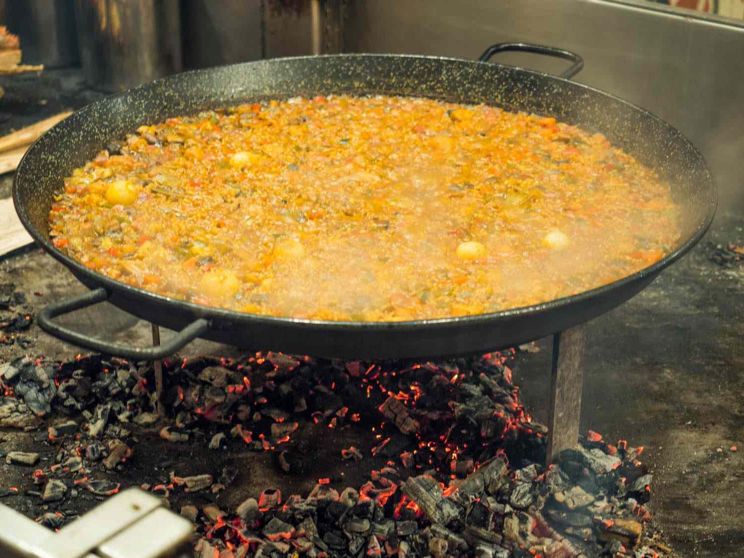 A large vegetable paella being finished over embers at Mercado Little Spain in NYC. The paella pan is held aloft on an iron stand, making it easy for the cook to manage the fire and embers below.