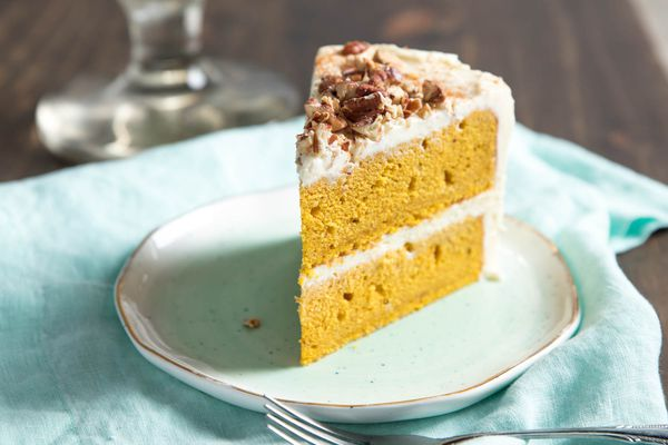 A slice of 2-layer pumpkin layer cake, with a white frosting and chopped pecans on top. The cake is on a small plate with a light blue linen underneath it.