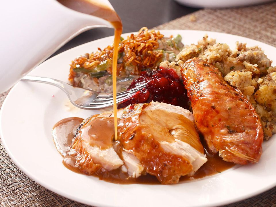 Pouring gravy over a serving plate of turkey and sides.