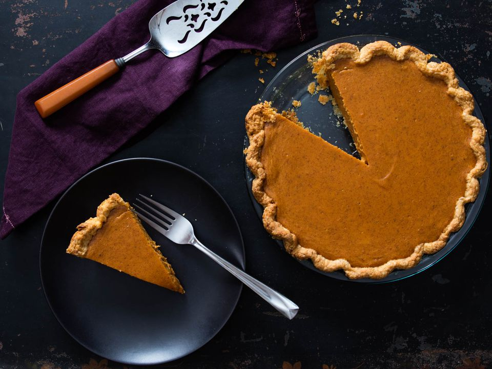 A wedge of sweet potato pie on a plate, next to the rest of the pie