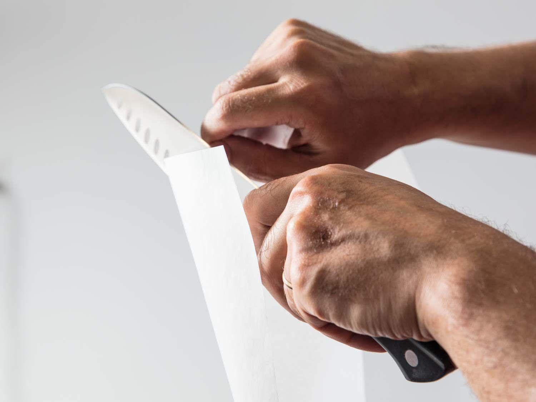 Testing santoku knife's sharpness by slicing paper