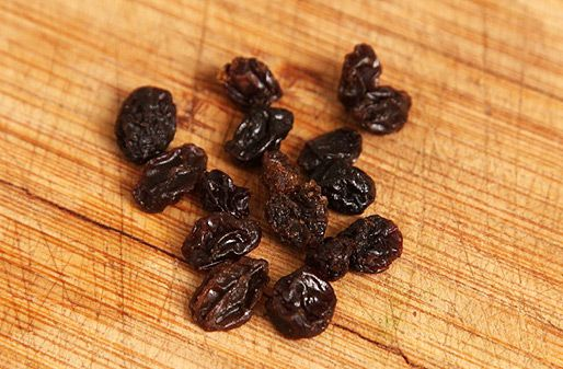 A small pile of raisins on a wood cutting board.