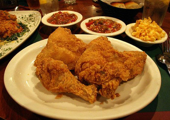 Plate of fried chicken with mac and cheese and other sides in the background.