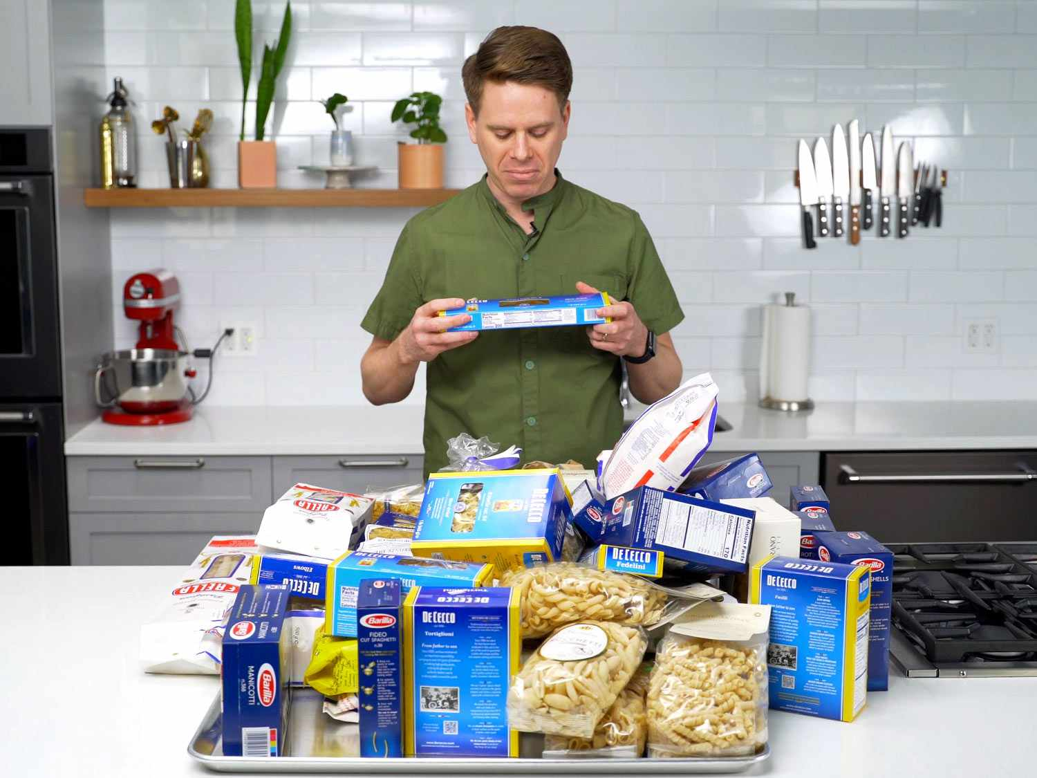 Sasha Marx standing in front of a pile of pasta products while frowning at a box of angel hair