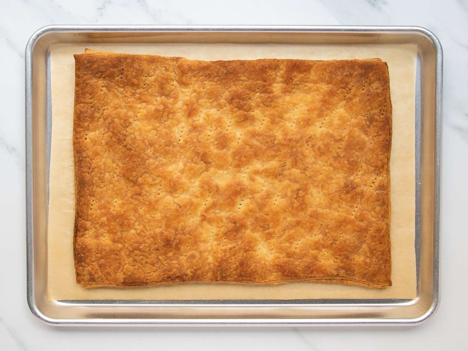 Fully baked puff pastry sheet set in rimmed baking sheet