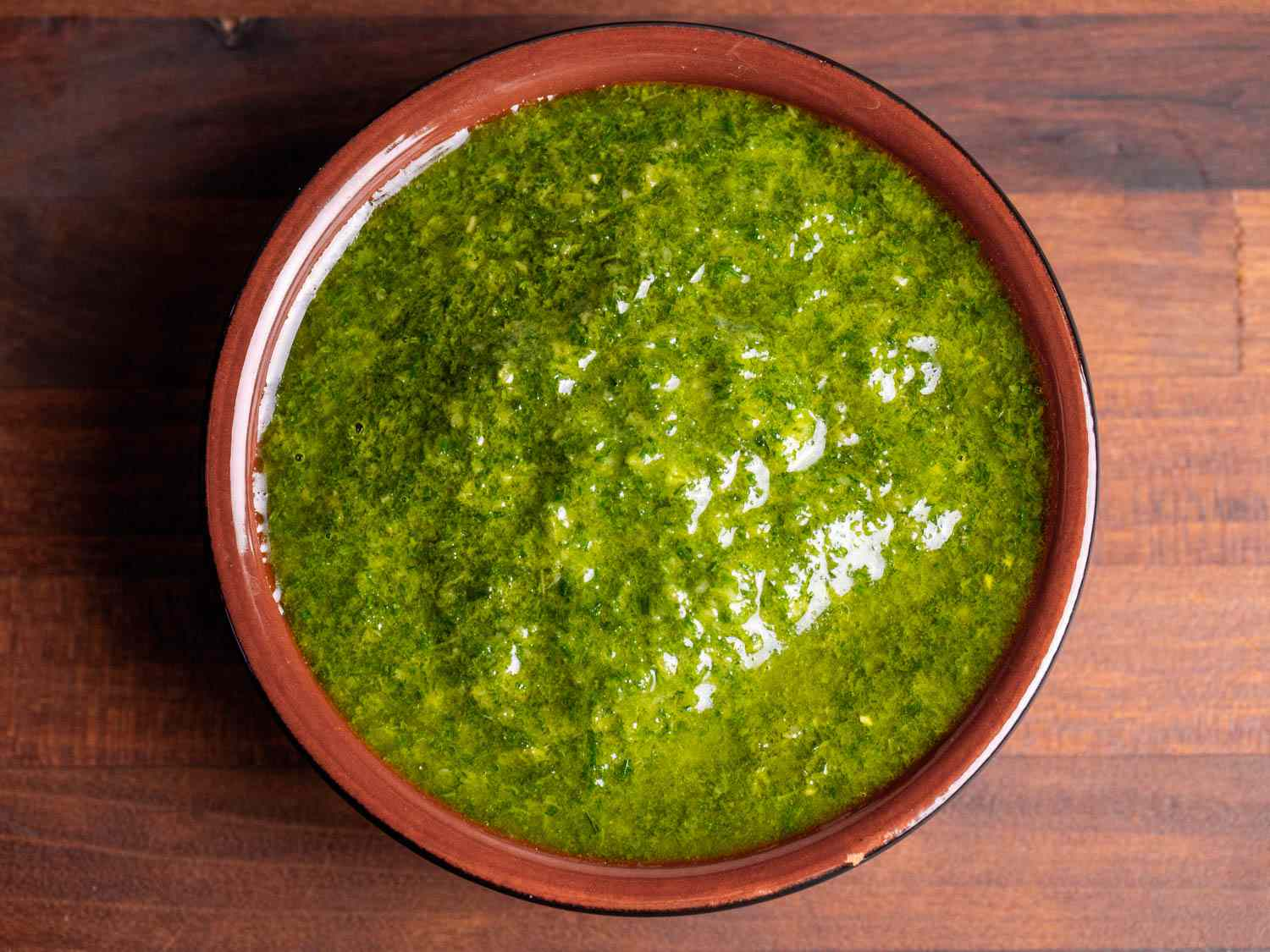 A small dish filled with bright green fennel frond pesto
