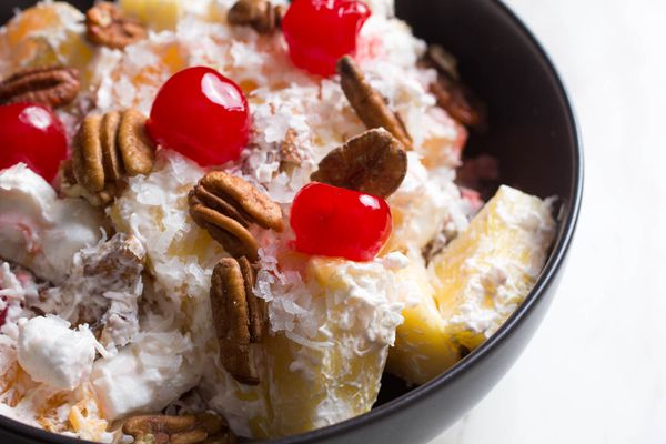 A bowl of ambrosia, a fruit salad with coconut, pineapple, pecans, mini-marshmallows, and cherries.